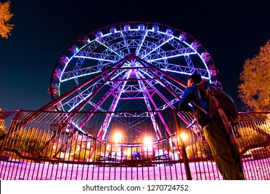 man stands in front of a glowing illumination by a ferris wheel, reflected in a puddle