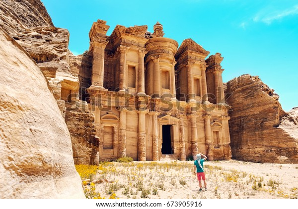 A man stands in front of the Monastery in the desert of Petra, near Wadi Musa, Jordan. Petra is one of the New7Wonders of the World and a UNESCO world heritage site.
