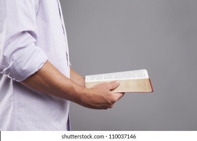 A man stands indoors holding a bible out in front of him with both hands.