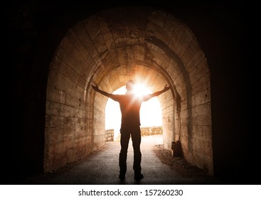 Man stands inside of old dark tunnel with shining sun in the end