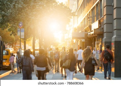 Man stands in the middle of a busy sidewalk looking at his cell phone while crowds of people walk around on 14th Street in Manhattan, New York City with the glow of sunlight in the background.
