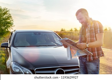 man stands near the car and looks at the map