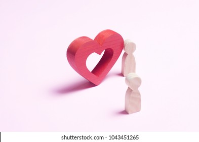 A man stands near the heart and confesses love on a pink background. A person makes an offer to marry his lover. The concept of love, caring, marriage, romantic relations. Love story. abstraction.