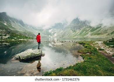 Man stands near Lake Hincovo Pleso in High Tatras mountains. Foggy cloudy spring weather. Popular travel and hiking destination.