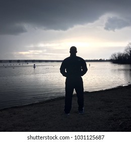 A man stands next the lake