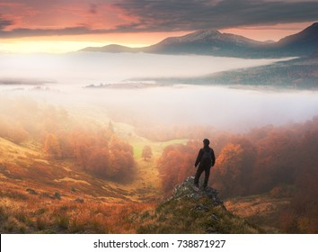 Man stands on background of misty autumn mountains