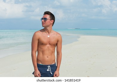man stands on the beach with the blue sea and the beautiful sky with white clouds