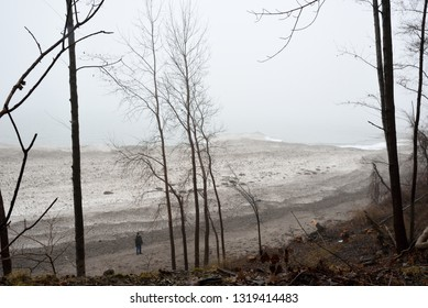 Man stands on beach looking up at the hillside. Perhaps lost in thought of a distant memory.