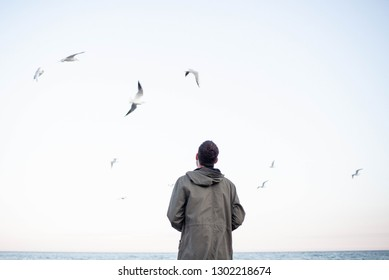 A man stands on the beach and seagulls are flying nearby. Enjoy the moment. Rest and relaxation by the sea. Weekend in nature. Life style