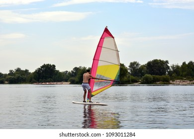 man stands on the Board in the water windsurfing