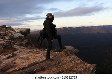 Man stands on a cliff and looks at the landscape from Lincoln Rock Lookout at sunrise in the Blue Mountains National Park in the Blue Mountains region of New South Wales, Australia