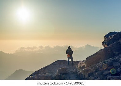 A man stands on the edge of a cliff on Mount Moses and looks at the sunrise in the mountains of Egypt.