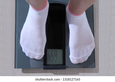 A man stands on electronic scales in white socks. Top view, close-up.