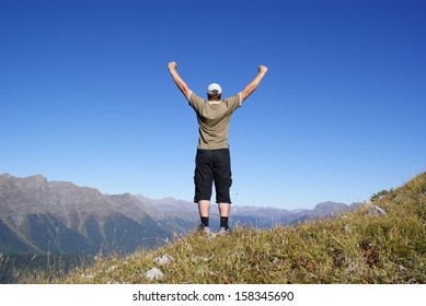 A man stands on a hillside with their hands up