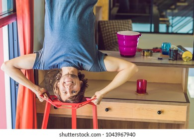 A man stands on his hands upside down in the kitchen
