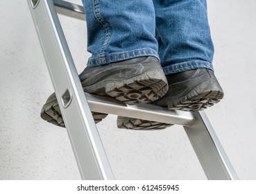 A man stands on a ladder