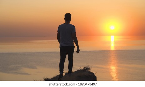 The man stands on the mountain edge on the seascape background