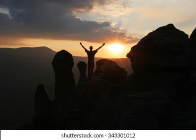 A man stands on the mountain raising his hands up and greets the rising sun