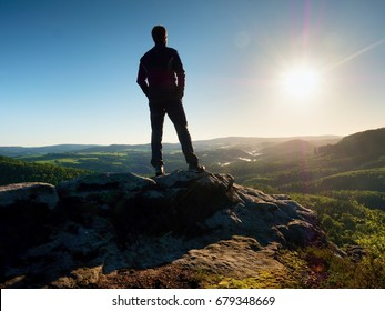 Man stands on the peak of sandstone rock  watching over valley to Sun. Beautiful moment the miracle of nature