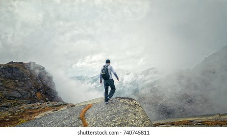 a man stands on the precipice of the mountain in the fog