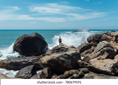 man stands on a rock and looks at the ocean, waves of waves fly upward