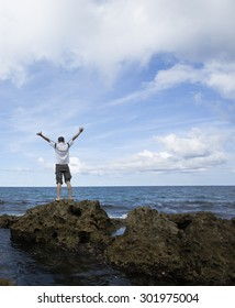 Man stands on rocks in front of the ocean with her hands up,China