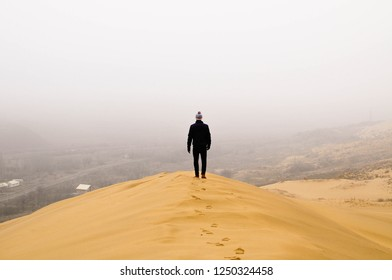 The man stands on sand of the little desert in the mountains. Dagestan, Russia
