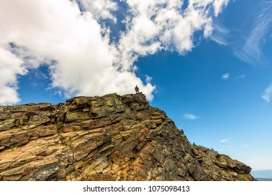 man stands on a steep cliff on the background of the sky