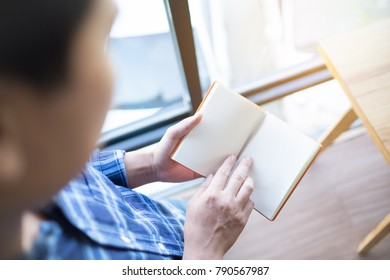Man stands open book in office.