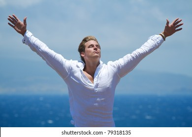 A man stands with outstretched arms on a cliffside overlooking the ocean.