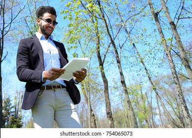 Man stands in park and typing number on phone.Guy dressed in black jacket and blue shirt. Male has short dark hair and beard. Concept of modern technologies order by phone