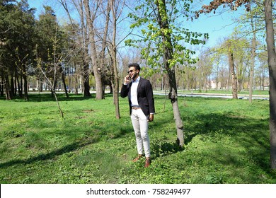 Man stands in park and typing number on phone.Guy dressed in black jacket and blue shirt. Male has short dark hair and beard. Concept of modern technologies order by phone.