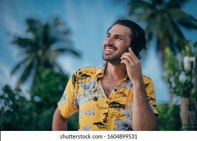 A man stands with a phone in his hands on a background of palm trees. A young guy is talking on the phone. He has a hawaiian shirt on a tropical island. Handsome man and bright positive emotions.