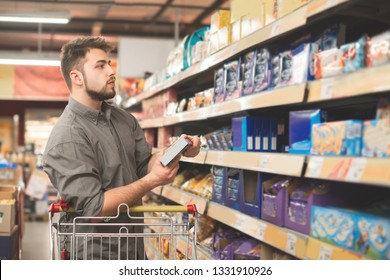 Man stands in a supermarket with a bundle of biscuits in his hands and looks at the shelf with sweets. The buyer buys cookies in a supermarket, looking at packaging with sweet