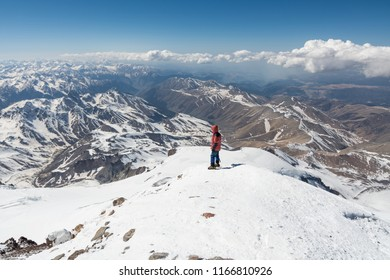 A man stands at the top of Elbrus 5642m and looks at the mountains.