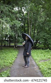 A man stands under a black umbrella