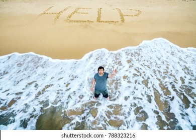 Man stands in the water and calls for help on the beach of uninhabited island. Inscription HELP on sand. Concept of uninhabited island and castaway. Lost in the sea and survivors on the island people.