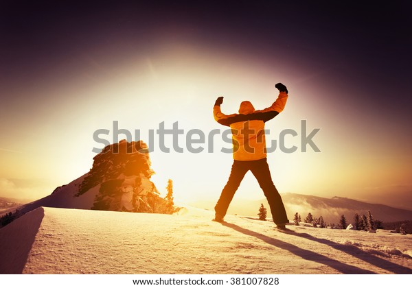 Man stands in winner pose on the top of a mountain. Sheregesh resort, Siberia, Russia