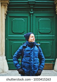A man stands in a winter jacket and a hat on the background of a green vintage door in Vienna, a man smiles
