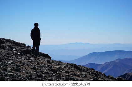 A man staning at the summit of Toubkal, Morocco, looking at the beautiful panorama of other muntain peaks and blue sky, after hiking to the end of the trail