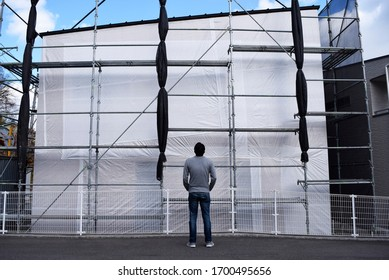 A man stares at his home in the middle of construction.