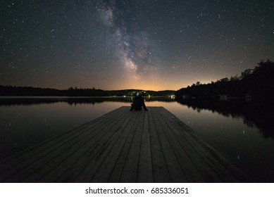 Man stargazing at the end of a dock in Muskoka, Ontario, Canada.