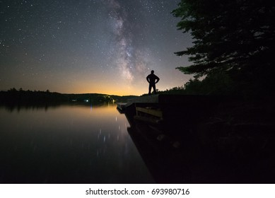 Man stargazing on a dock in Muskoka, Ontario, Canada.