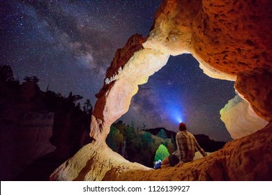 A man stargazing under an arch in the Utah desert, USA.