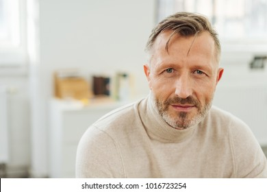 Man staring at the camera with an intense penetrating look as he leans forwards