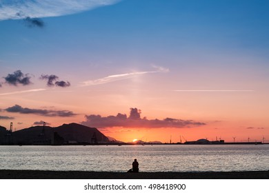 Man staring at sunset on the beach. When you see the sunset you get relaxation, a release of tension, a return to equilibrium. Relaxing is the quality or state of being tranquil, calm, and worry-free.