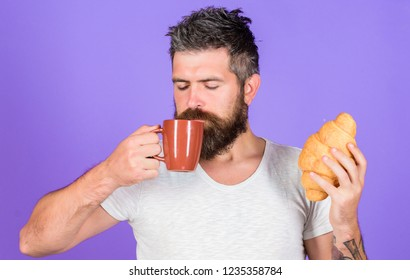 Man start morning with cup of coffee and fresh croissant. Bearded hipster enjoy breakfast drink coffee. Morning tradition concept. But first coffee. Enjoy every sip of coffee. Perfect match.
