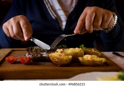 Man started eat medium roasted veal steak . Hands close-up view.
