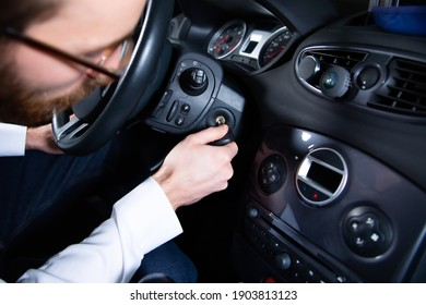 Man starting a car engine with an ignition key. Putting a key into the ignition to start an auto, a vehicle.