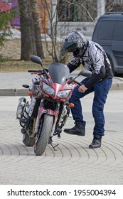 A man starts his motorcycle with a kickstarter in an empty city parking lot